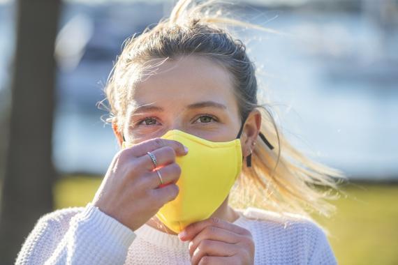 Chica ajustando su mascarilla para protegerse del coronavirus.