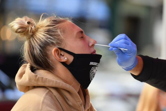 Un sanitario realiza una PCR a una estudiante en Nueva York.