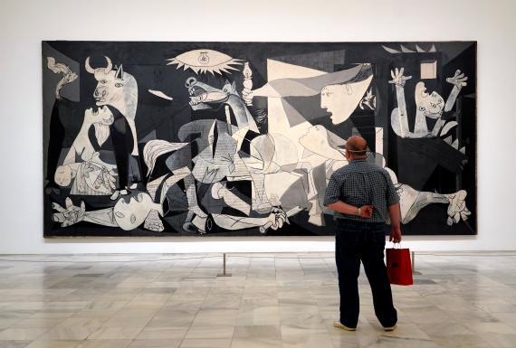Un hombre frente al cuadro del Guernica de Pablo Picasso.
