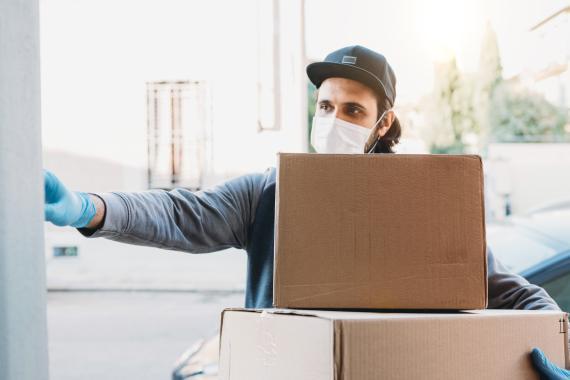 Un hombre con varios paquetes llama a una puerta.