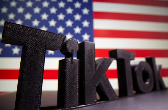 Logotipo en 3D de TikTok delante de una bandera de Estados Unidos.