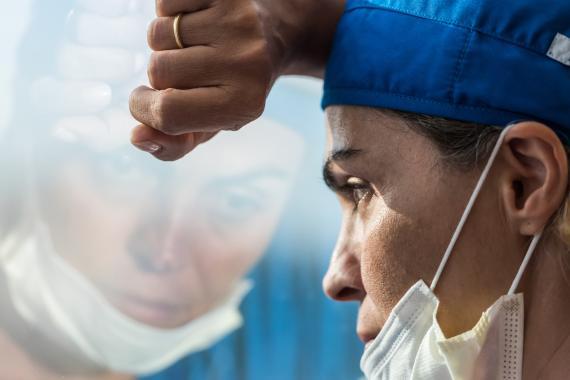 Una médico se apoya contra el cristal con cara de cansancio y tristeza.