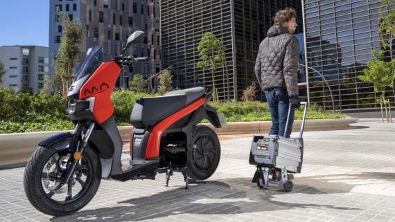Una moto eléctrica Seat MÓ con su batería extraíble, que se lleva en un carrito.