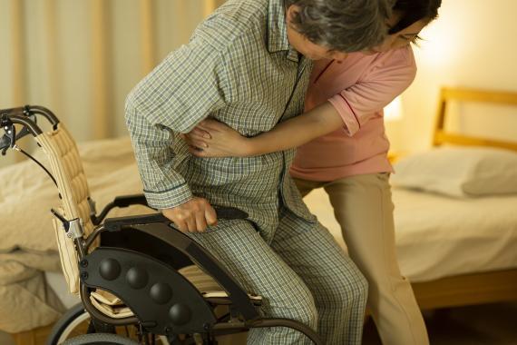 Una mujer ayuda a levantarse a un hombre que está en silla de ruedas.