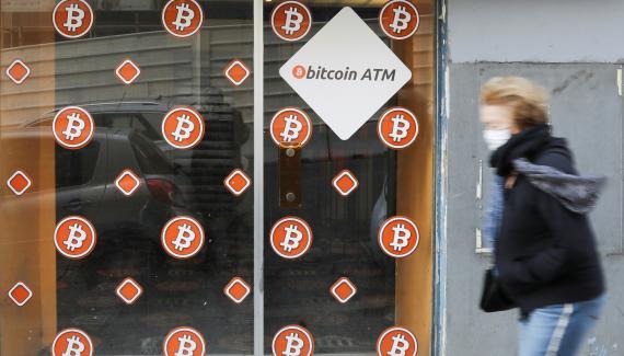 Una mujer con mascarilla pasa ante un cajero autómatíco de bitcoin en Marsella (Francia)