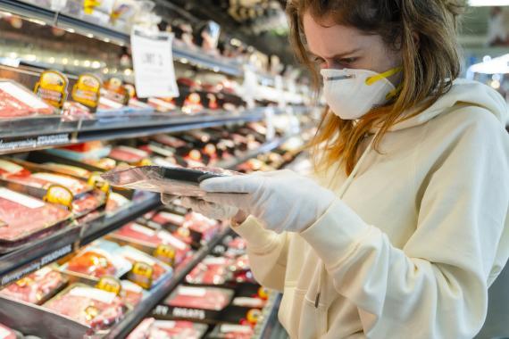 Una mujer mira la etiqueta de la carne en un supermercado.