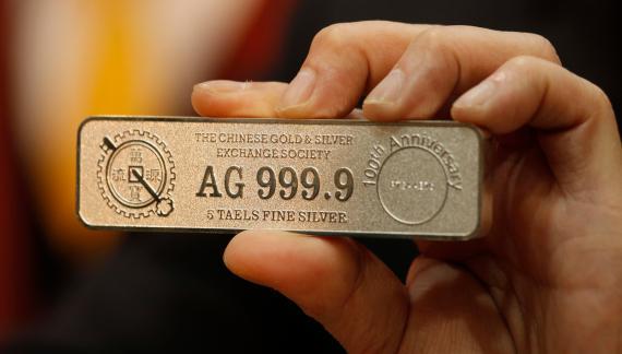 Un operario de la bolsa de Hong Kong sostiene un lingote de plata