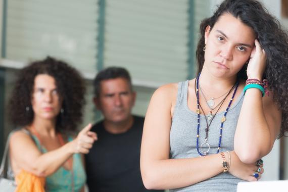 Unos padres señalan a una adolescente.