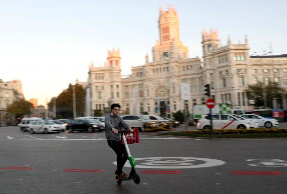 Un patinete eléctrico compartido de la marca estadounidense Lime pasa por delante del Ayuntamiento de Madrid.