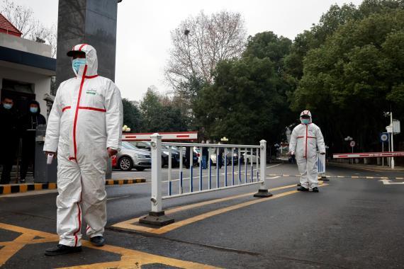 Personal de seguridad vigila durante la visita de los miembros del equipo de la OMS encargado de investigar los orígenes del  coronavirus en Wuhan