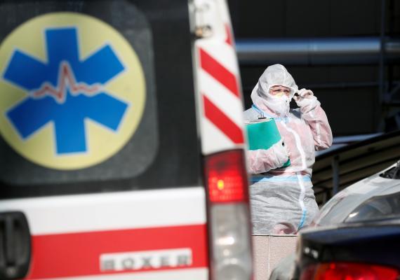 Un trabajador sanitario con EPI cerca de una ambulancia.