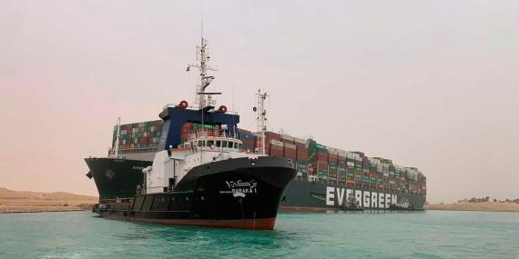 Un barco navega ante un enorme portacontenedores llamado Ever Given, varado el miércoles 24 de marzo de 2021 en el Canal de Suez, Egipto.