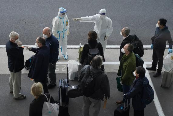 A worker in protective GEAR directs members of the World Health Organization team at the airport in Wuhan, China, January 14, 2021.