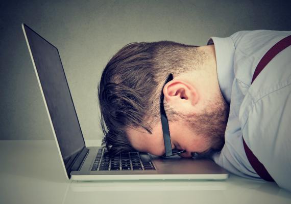 Un hombre con la cara apoyada en el teclado del ordenador.