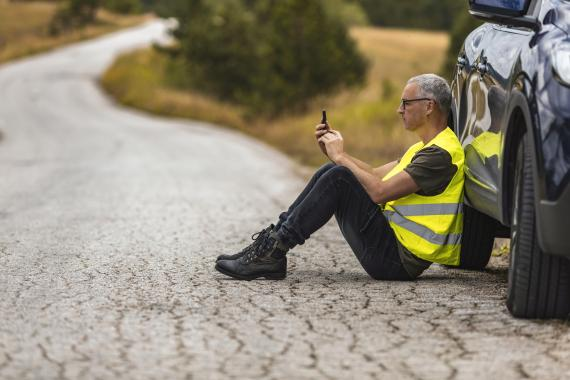 Un hombre con chaleco reflectante mira el móvil apoyado en el coche.