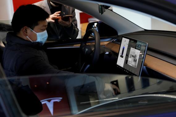 Un hombre prueba un Tesla Model Y en China
