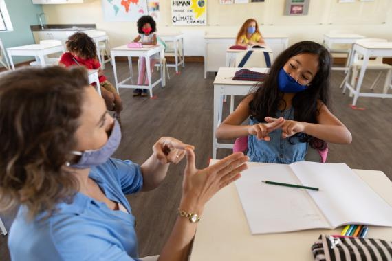 Una maestra y su alumna hablan en lengua de signos.