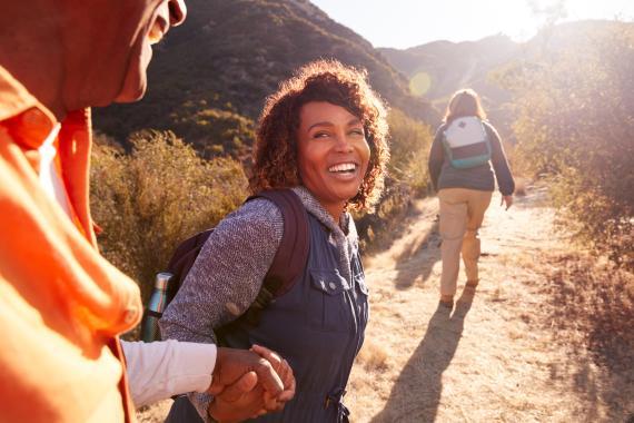 Una mujer agarra a un hombre en una ruta de senderismo.