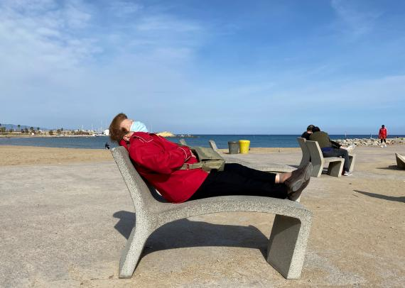 Una mujer descansa en la playa con la mascarilla puesta