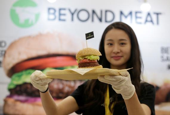 mujer sosteniendo hamburguesa de Beyond Meat