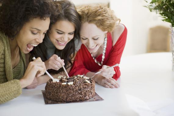 Mujeres comiendo una tarta de chocolate.