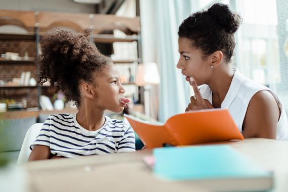 Una niña le saca la lengua a su madre mientras hacen los deberes.