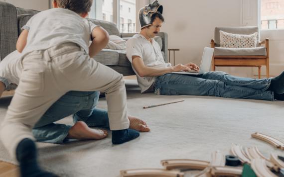 Un padre trata de trabajar con un casco en la cabeza, mientras sus hijos juegan.