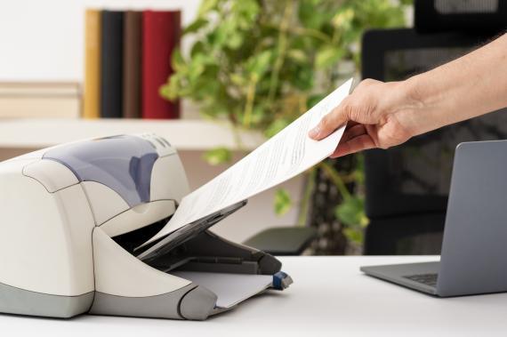 Una persona recogiendo papeles de una impresora