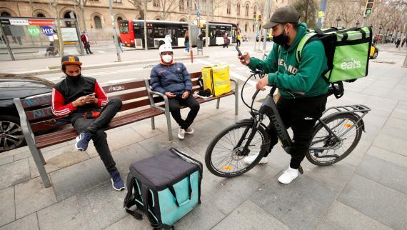 Riders de Glovo, Deliveroo y Uber Eats esperan pedidos en un banco en Barcelona