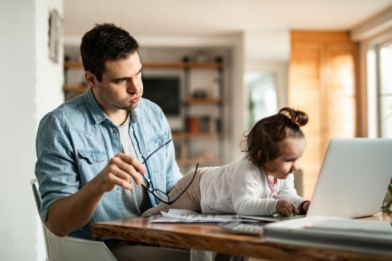 Un señor trata de trabajar con su hija encima.