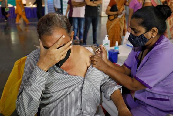 Un hombre es vacunado contra el virus del COVID-19 en India.
