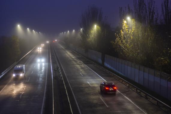 Varios vehículos circulan por una autopista por la noche con lluvia.