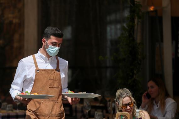 Camarero con mascarilla sirve en una terraza en Roma, Italia.