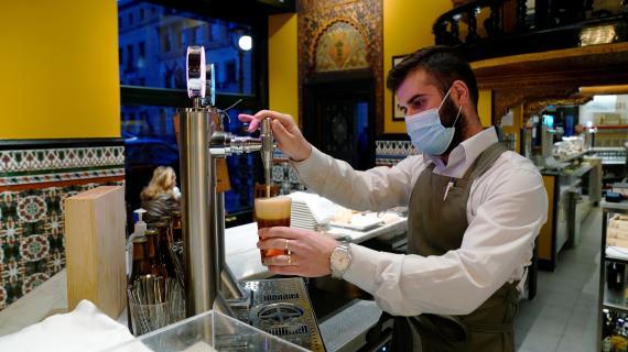 Un camarero tira una caña de cerveza en un bar de Madrid