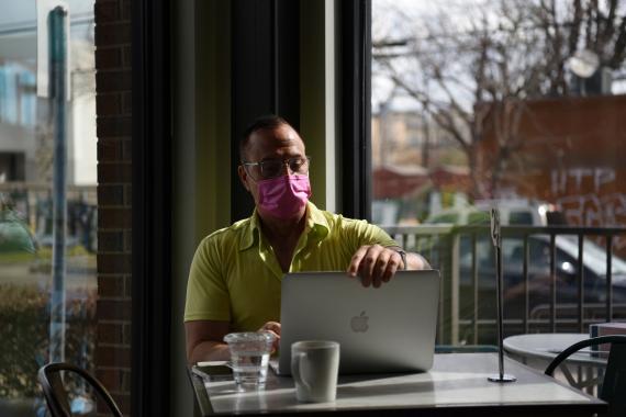 Un hombre en una cafetería con una mascarilla y un ordenador.