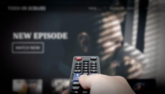 Un hombre con un mando de televisión viendo la tele