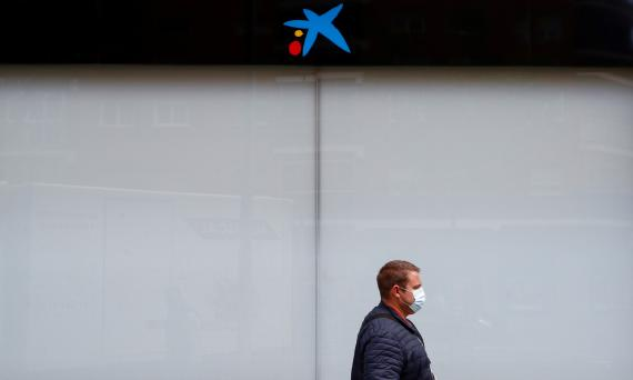 Un hombre con mascarilla pasa ante una oficina cerrada de CaixaBank