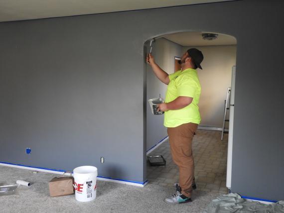 Un hombre pinta en una casa.