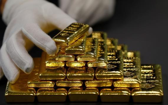 Hombre sujetando una onza de oro