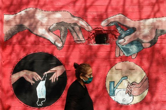 Una mujer anda por la calle, donde hay un grafiti inspirado en la pandemia.