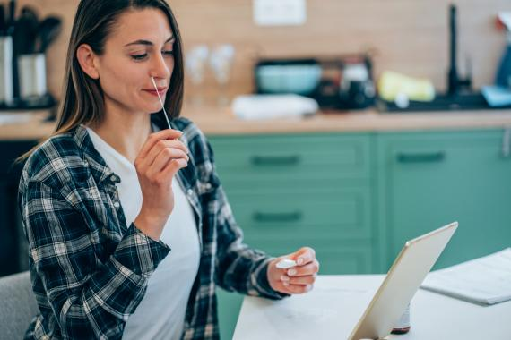 Una mujer se hace un test PCR mientras mira una tablet.