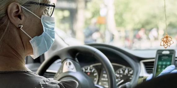 Una mujer con mascarilla y guantes conduce un coche.