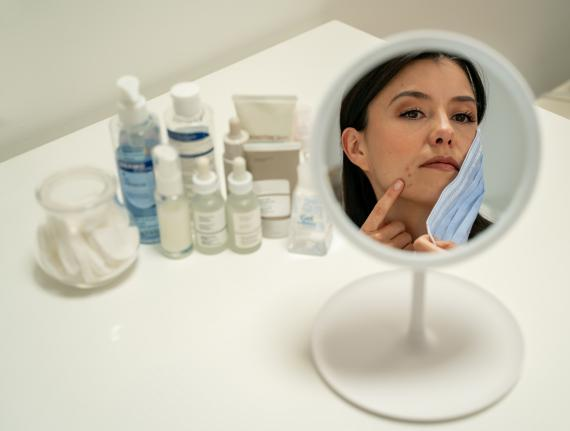 Una mujer se mira unas irritaciones en la piel en el espejo.