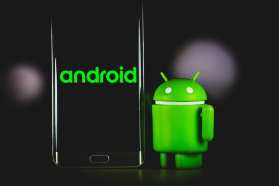 Un muñeco de Android al lado de un móvil