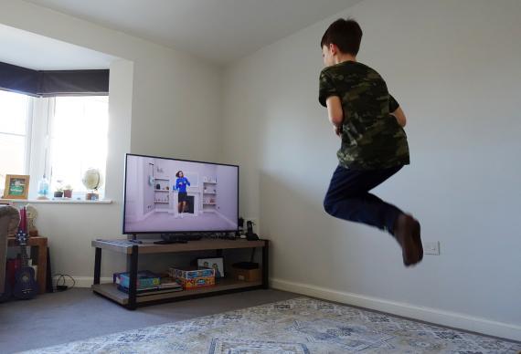 Un niño realiza ejercicio a través de un vídeo de YouTube durante la cuarentena en Reino Unido.