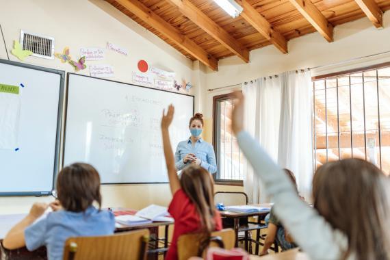 Varios niños y niñas levantan la mano en clase.
