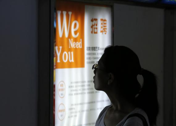 chica observa cartel de búsqueda de trabajo