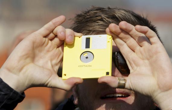 Un hombre contempla un eclipse a través de un disquete en Praga.