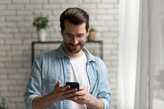 Hombre lee un mensaje en su móvil