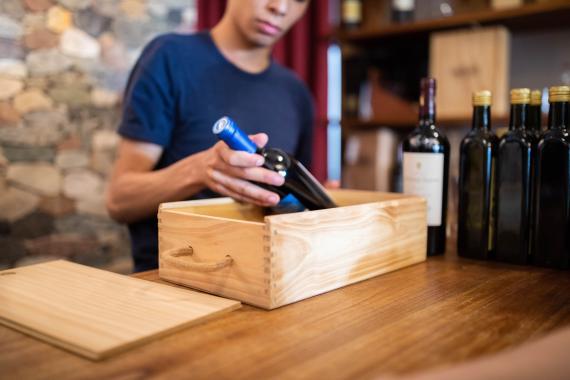 Un hombre sacando botellas de vino de una caja